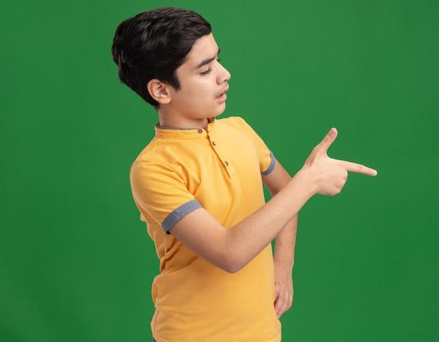 허리에 손을 대고 보고 녹색 벽에 고립 된 측면을 가리키는 감동 젊은 백인 소년