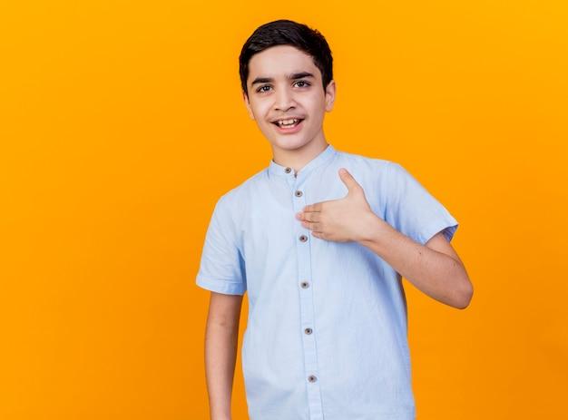 コピースペースでオレンジ色の背景に分離された胸に触れるカメラを見て感動の若い白人少年