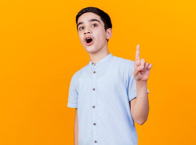 Impressionato giovane ragazzo caucasico che guarda l'obbiettivo alzando il dito isolato su sfondo arancione con spazio di copia