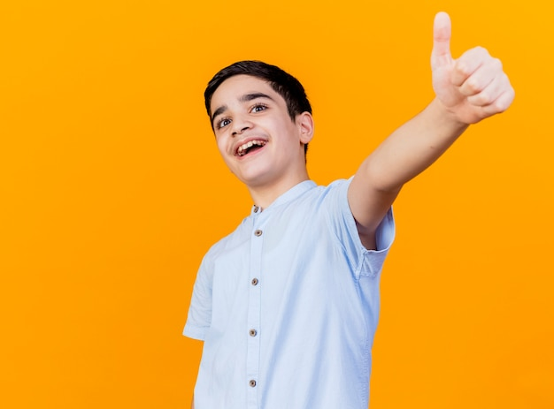 Impressed young caucasian boy looking at camera showing thumb up isolated on orange background with copy space