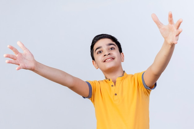 Впечатленный молодой кавказский мальчик смотрит прямо, приветствуя кого-то с широко распростертыми объятиями, изолированными на белом фоне