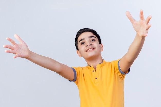 Impressionato giovane ragazzo caucasico guardando dritto saluto qualcuno con le braccia spalancate isolato su sfondo bianco