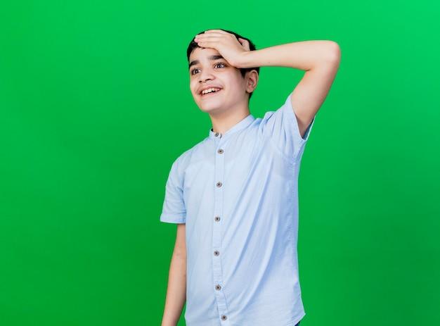 Impressionato giovane ragazzo caucasico guardando dritto tenendo la mano sulla testa isolata sulla parete verde con lo spazio della copia