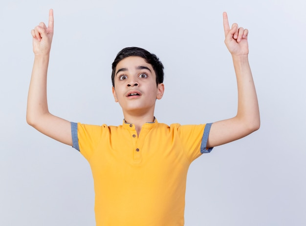 Impressed young caucasian boy looking straight pointing up isolated on white background