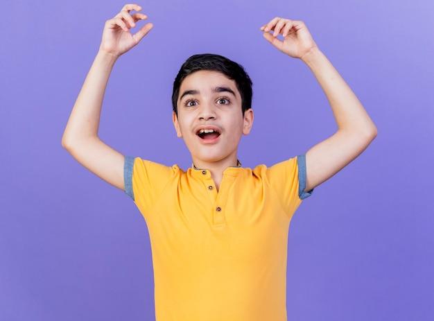 보라색 벽에 고립 된 손을 똑바로 올리는 감동 어린 백인 소년