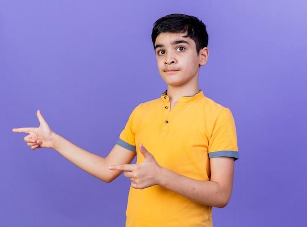 コピースペースで紫色の壁に隔離された側を指している印象的な若い白人の少年