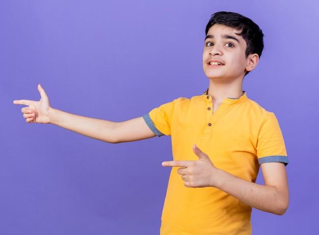 紫色の壁に隔離された側を指している印象的な若い白人の少年