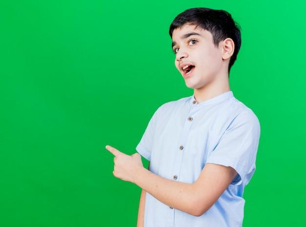 コピースペースのある緑の壁に孤立した後ろを指している印象的な若い白人の少年