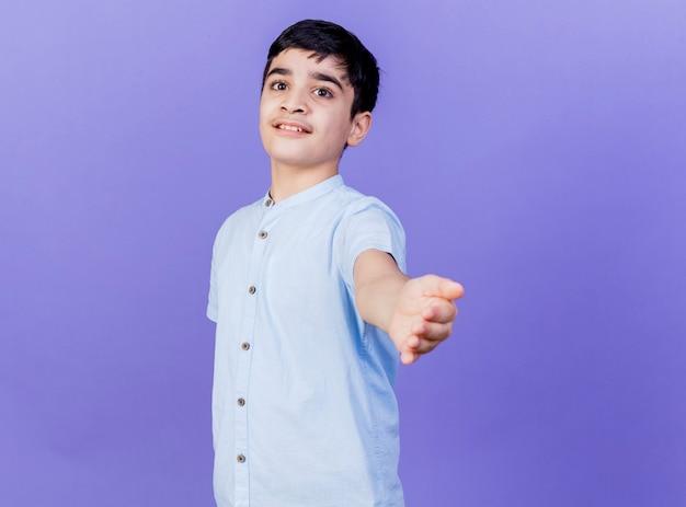 コピースペースで紫色の背景に分離されたカメラに向かって手を伸ばしているカメラを見て縦断ビューに立っている印象的な若い白人の少年