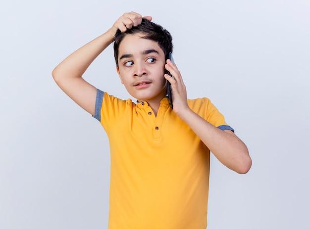 白い背景で隔離の側を見て髪をつかんで電話で話している印象的な若い白人の少年