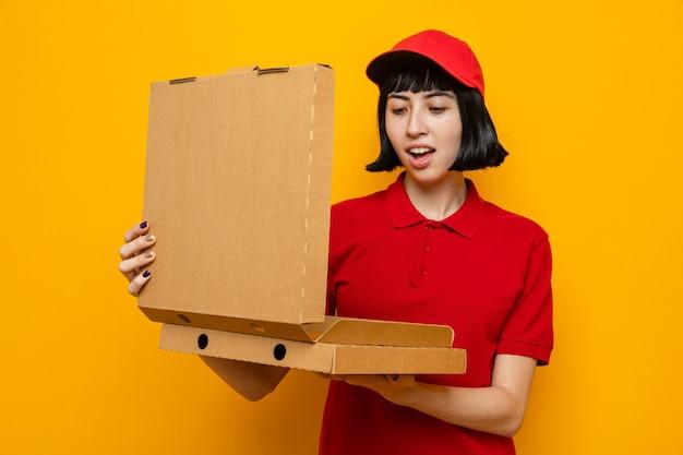 Impressionata giovane ragazza delle consegne caucasica che tiene in mano e guarda le scatole della pizza