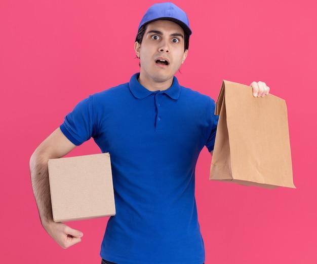 Impressionato giovane fattorino caucasico in uniforme blu e cappuccio con scatola di cartone e pacchetto di carta