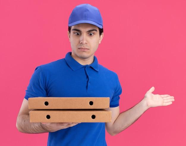 Impressionato giovane fattorino caucasico in uniforme blu e berretto che tiene e guarda i pacchetti di pizza che mostrano la mano vuota