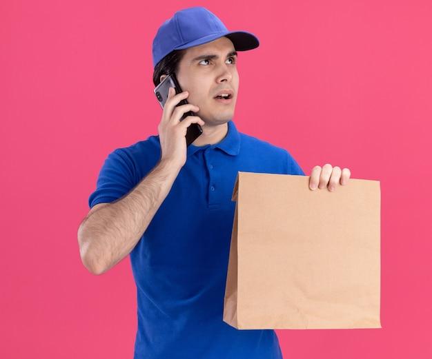 Impressionato giovane fattorino caucasico in uniforme blu e cappuccio che tiene un pacchetto di carta parlando al telefono guardando in alto isolato su parete rosa on
