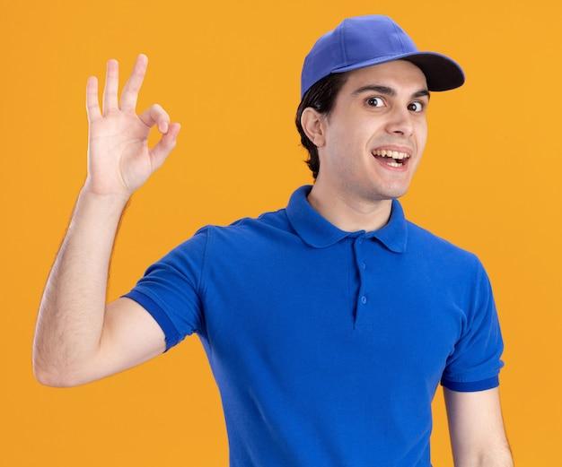 青い制服とオレンジ色の壁に分離されたokサインをしているキャップで感銘を受けた若い白人配達人