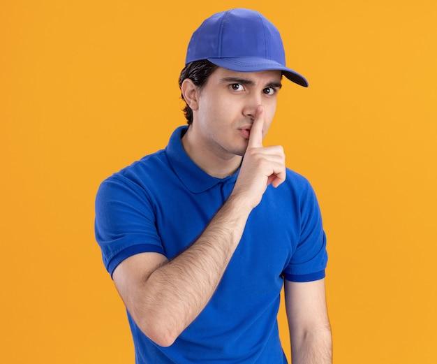 파란색 유니폼을 입은 백인 배달원과 주황색 배경에 침묵 제스처를 취하는 모자에 깊은 인상을 받았습니다.