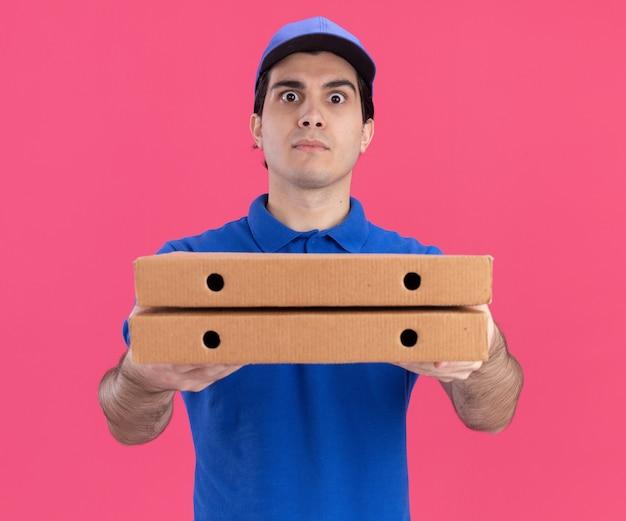 Впечатленный молодой кавказский доставщик в синей форме и кепке, протягивающий пакеты с пиццей
