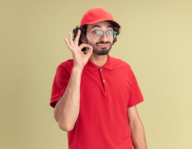 赤い制服を着た若い白人配達人に感銘を受け、おいしいジェスチャーをしている眼鏡をかけた帽子
