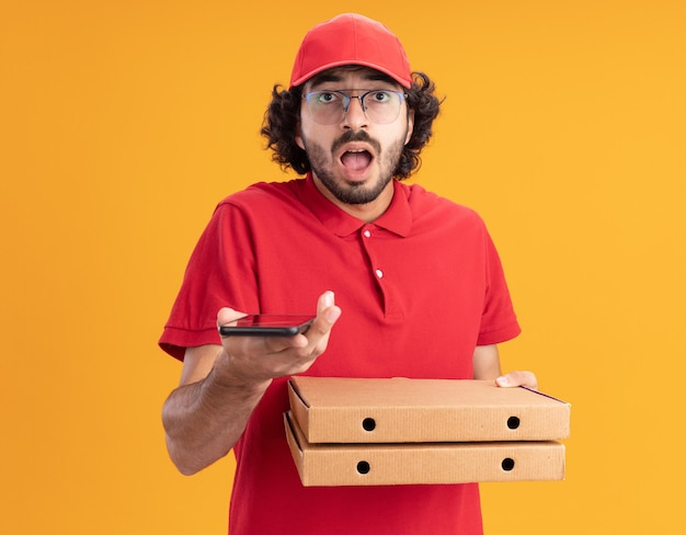 주황색 벽에 격리된 피자 패키지와 휴대폰을 들고 안경을 쓴 빨간 유니폼과 모자를 쓴 젊은 백인 배달원