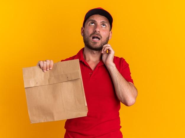 Impressionato giovane fattorino caucasico in uniforme rossa e cappuccio che tiene in mano un pacchetto di carta toccando il viso guardando in alto isolato sulla parete arancione con spazio per le copie