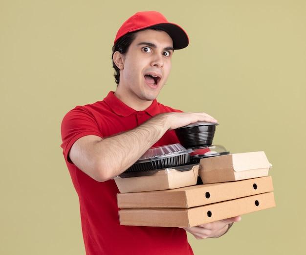 Impressionato giovane fattorino caucasico in uniforme rossa e berretto con pacchi di pizza con contenitori per alimenti e pacchetti di carta per alimenti su di essi isolati sul muro verde oliva