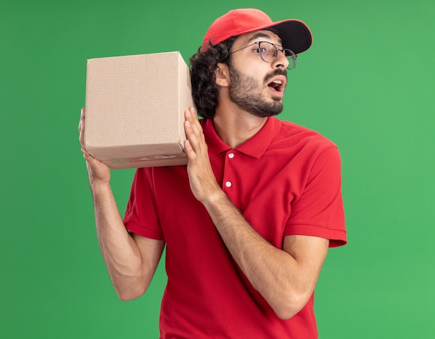 Impressionato giovane fattorino caucasico in uniforme rossa e berretto con gli occhiali che tengono la scatola delle carte vicino alla testa guardando in basso