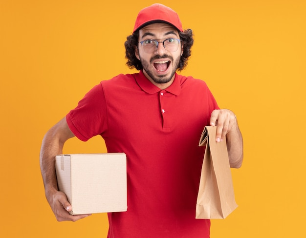 Impressionato giovane fattorino caucasico in uniforme rossa e berretto con gli occhiali che tengono scatola di cartone e pacchetto di carta isolato su parete arancione