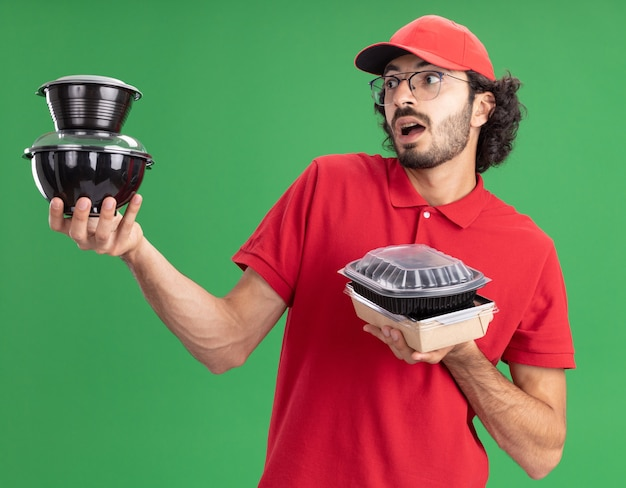 Impressed young caucasian delivery man in red uniform and cap wearing glasses holding paper food package and food containers looking at food containers