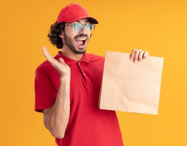 Impressionato giovane fattorino caucasico in uniforme rossa e berretto con gli occhiali che tengono un pacchetto di carta che mostra la mano vuota