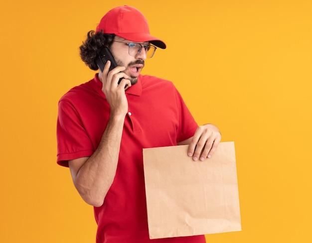 Impressionato giovane fattorino caucasico in uniforme rossa e berretto con gli occhiali che tiene in mano un pacchetto di carta che parla al telefono guardando in basso