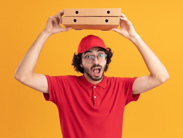 Impressionato giovane fattorino caucasico in uniforme rossa e berretto con gli occhiali che tengono i pacchetti di pizza sopra la testa