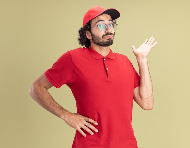 Impressed young caucasian delivery man in red uniform and cap wearing glasses keeping hand on waist showing empty hand