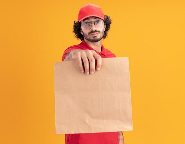 Impressionato giovane fattorino caucasico in uniforme rossa e berretto con gli occhiali che allungano il pacchetto di carta verso la telecamera