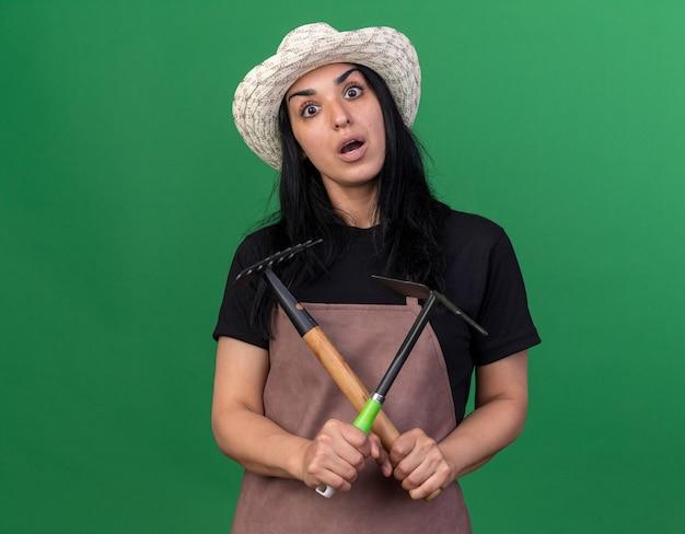 제복을 입고 갈퀴와 괭이 갈퀴를 들고 모자를 쓴 젊은 백인 정원사 소녀가 건넜습니다.