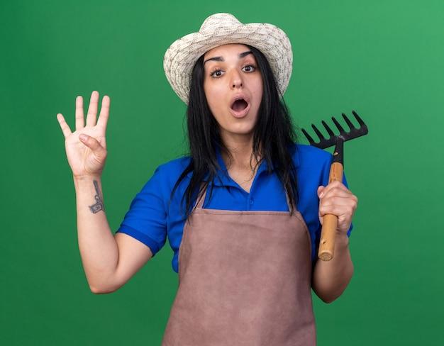 手で4つを示す熊手を保持している制服と帽子を身に着けている印象的な若い白人の庭師の女の子