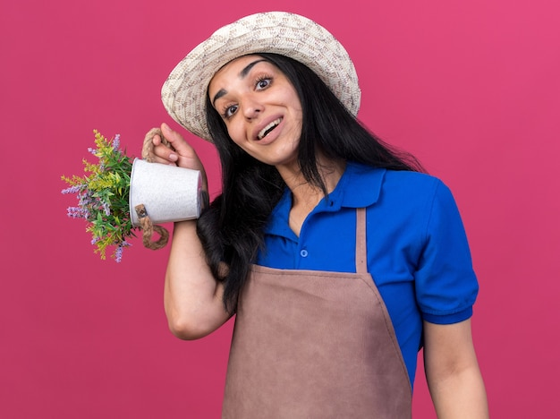 Impressed young caucasian gardener girl wearing uniform and hat holding flowerpot  isolated on pink wall