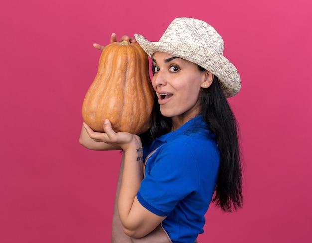 Impressionato giovane giardiniere caucasica ragazza che indossa uniforme e cappello