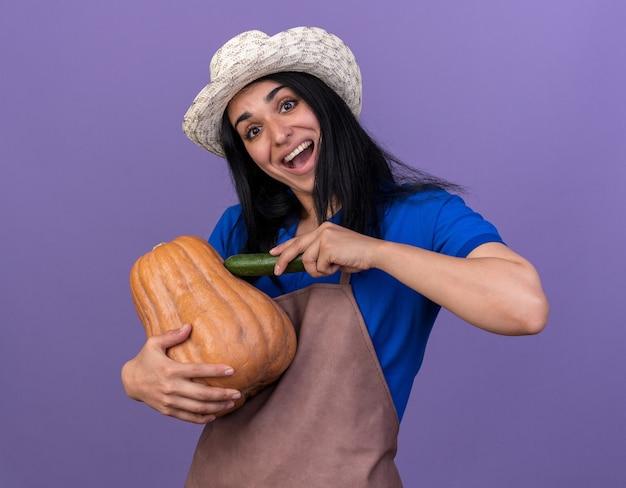 キュウリでそれに触れるバターナッツカボチャを保持している制服と帽子を身に着けている印象的な若い白人の庭師の女性