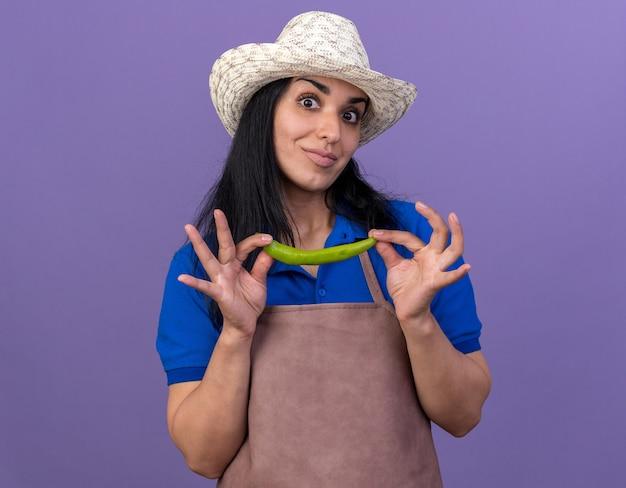 Впечатленная молодая кавказская женщина-садовник в униформе и шляпе с перцем