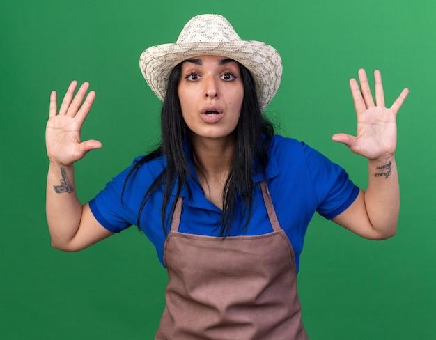 Впечатленная молодая кавказская женщина-садовник в униформе и шляпе показывает пустые руки