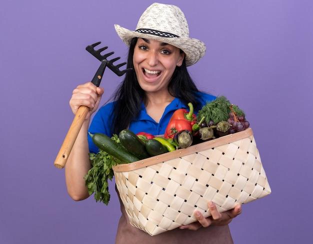 Impressionato giovane giardiniere caucasica donna che indossa l'uniforme e cappello con cesto di verdure e rastrello