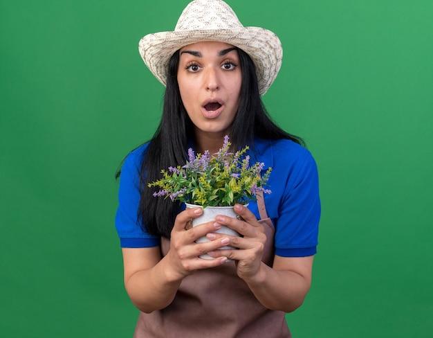 Impressionato giovane giardiniere caucasica donna che indossa l'uniforme e cappello che tiene vaso di fiori