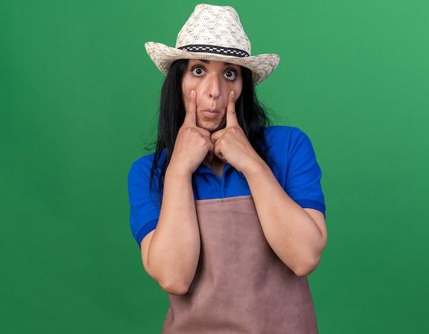 Impressionato giovane giardiniere caucasica donna che indossa l'uniforme e il cappello che tira giù le palpebre