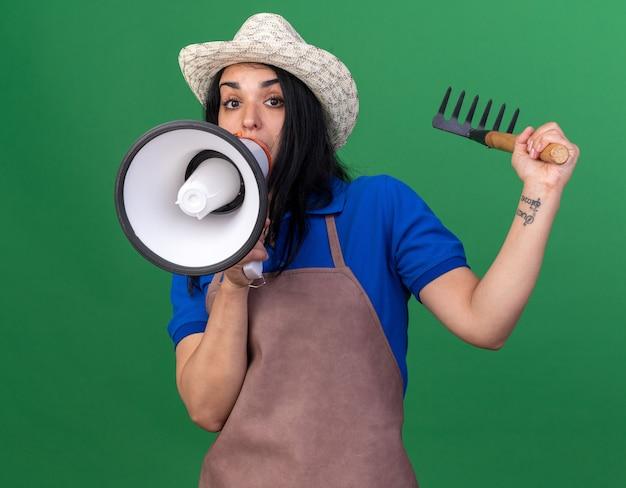 Impressionato giovane giardiniere caucasica donna che indossa l'uniforme e rastrello che alza il cappello parlando dall'altoparlante