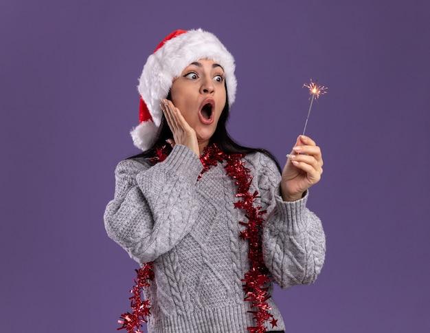 クリスマスの帽子と見掛け倒しの花輪を首の周りに身に着けている印象的な若い白人の女の子は、紫色の背景で隔離の顔に手を保ちながら休日の線香花火を保持し、見ています