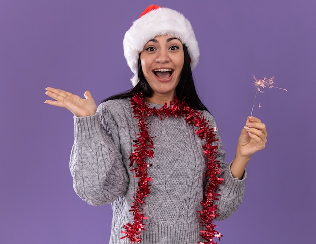 Впечатленная молодая кавказская девушка в рождественской шляпе и гирлянде из мишуры на шее держит праздничный бенгальский огонь, глядя в камеру, показывая пустую руку, изолированную на фиолетовом фоне