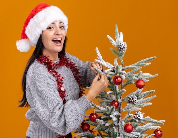 オレンジ色の背景に分離されたカメラを見てそれを飾るクリスマスツリーの近くの縦断ビューに立っている首の周りにクリスマス帽子と見掛け倒しの花輪を身に着けている印象的な若い白人の女の子