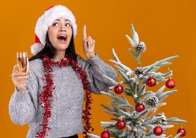クリスマス帽子と見掛け倒しの花輪を着て、オレンジ色の壁に孤立した上向きの側を見てシャンパンのグラスを持って飾られたクリスマス ツリーの近くに立っている印象的な若い白人の女の子