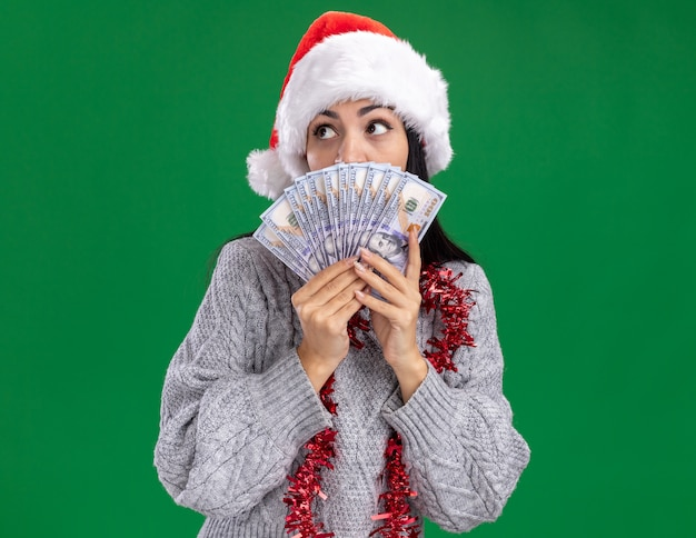 Impressed young caucasian girl wearing christmas hat and tinsel garland around neck holding money looking at side from behind it isolated on green wall with copy space