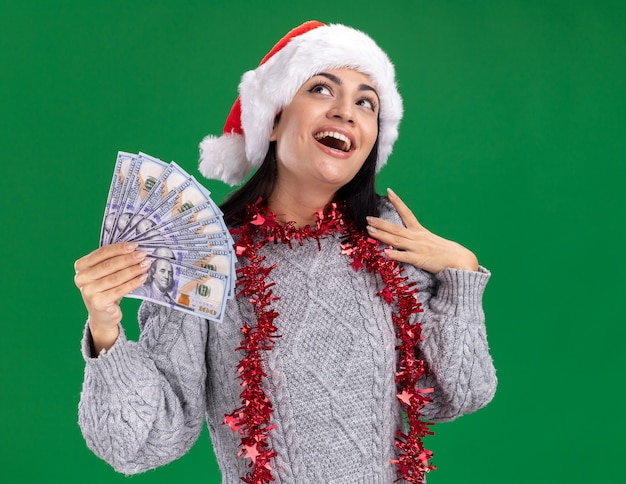 Impressed young caucasian girl wearing christmas hat and tinsel garland around neck holding money touching shoulder looking up isolated on green background